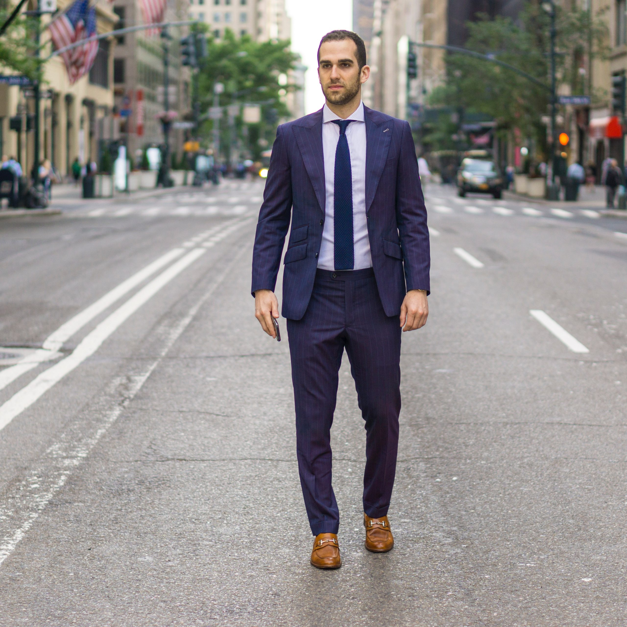 man in black suit standing on road during daytime