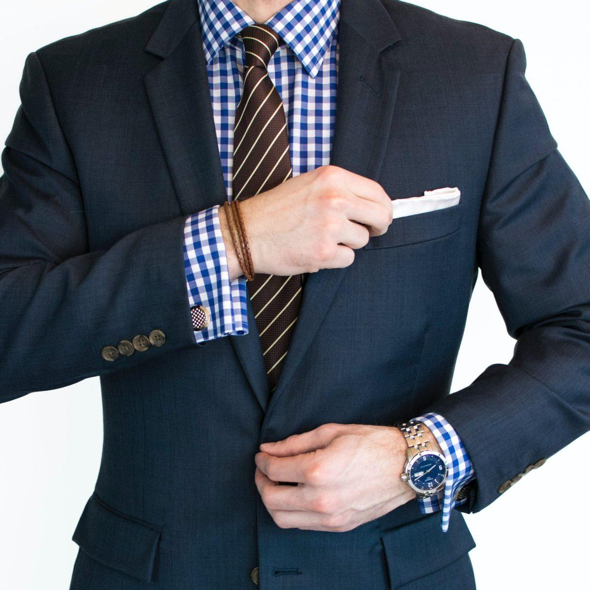 man in black suit jacket wearing gold watch